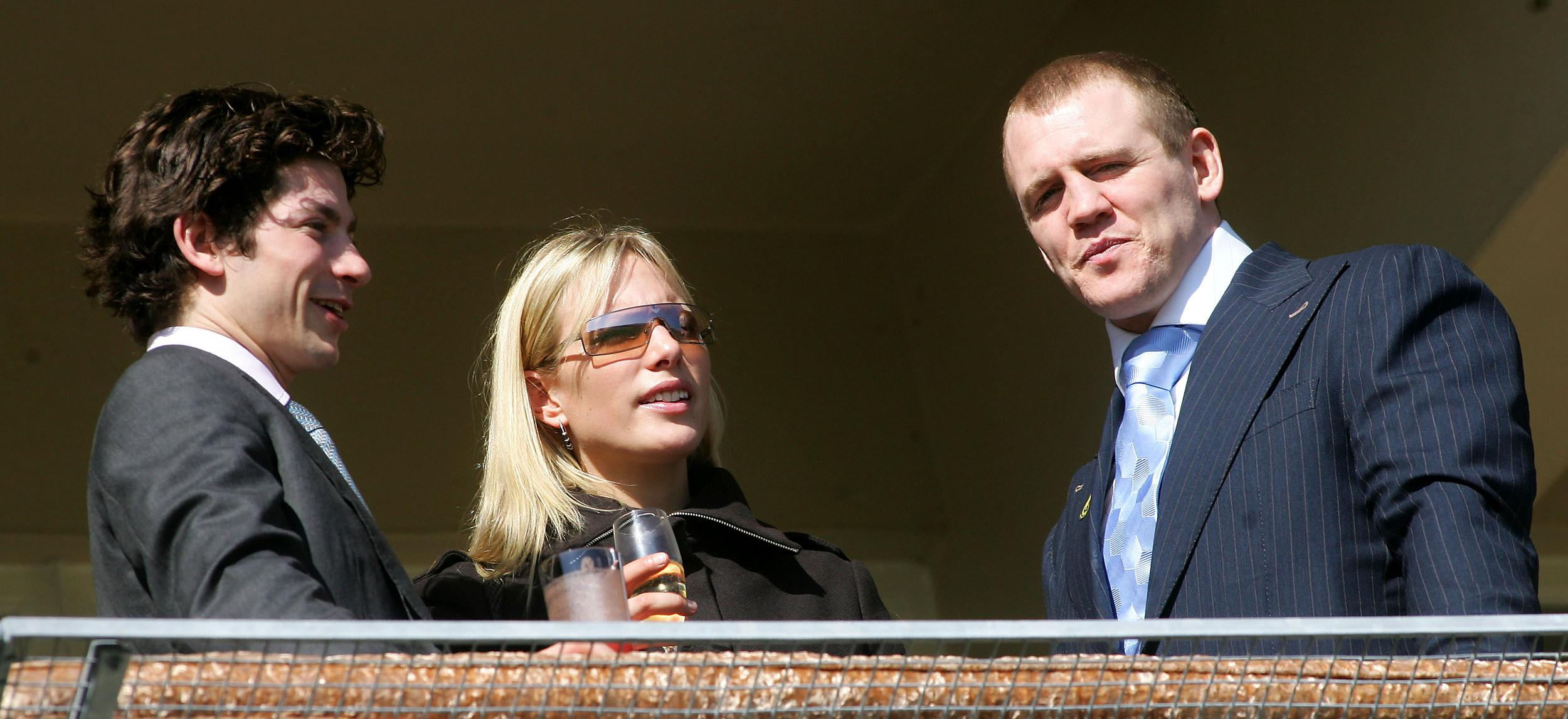 Britain's Phillips talks with England rugby player Tindall on the final day of the Cheltenham National Hunt Festival.  Britain's Zara Phillips (C), granddaughter of Queen Elizabeth, has a drink with boyfriend England rugby player Mike Tindall (R) and an unidentifed man on the final day of the Cheltenham National Hunt Festival meeting in Gloucestershire, central England, March 18, 2005. REUTERS/Mike Finn-Kelcey
