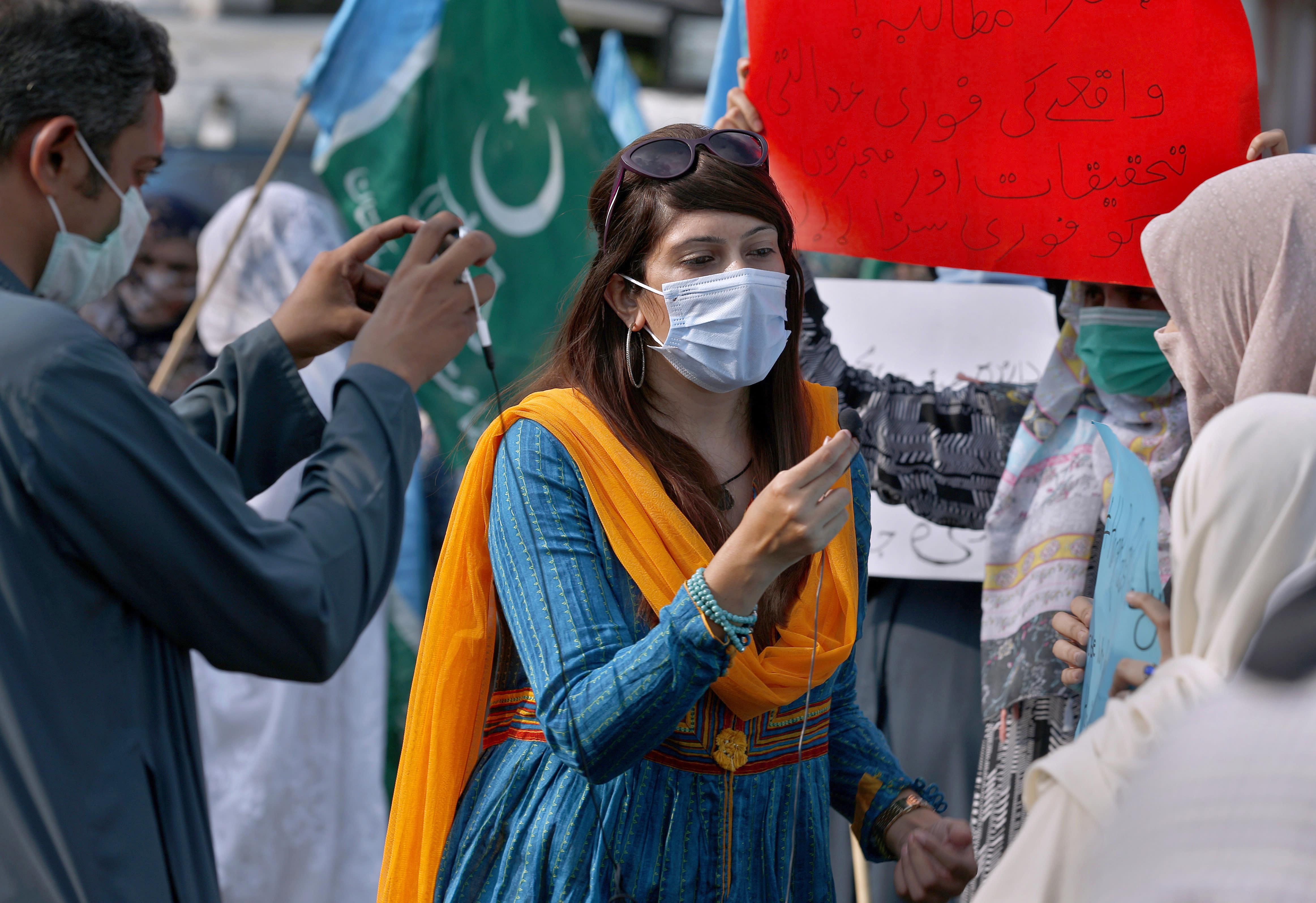 In this Friday, Sept. 11, 2020 photo, Mona Khan, a freelance female journalist, interviews during a rally, in Islamabad, Pakistan. Social media attacks against Pakistan's women journalists have been vile and vicious, some threatening rape, others even threatening death and the culprits are most often allied to the ruling party, even prompting the Committee to Protect Journalists to issue a statement on Friday, Sept. 18, condemning the relentless attacks. (AP Photo/Anjum Naveed)