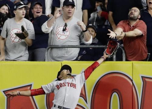 Red Sox right fielder Mookie Betts battles a fan for Chris Carter's fly ball. (AP)