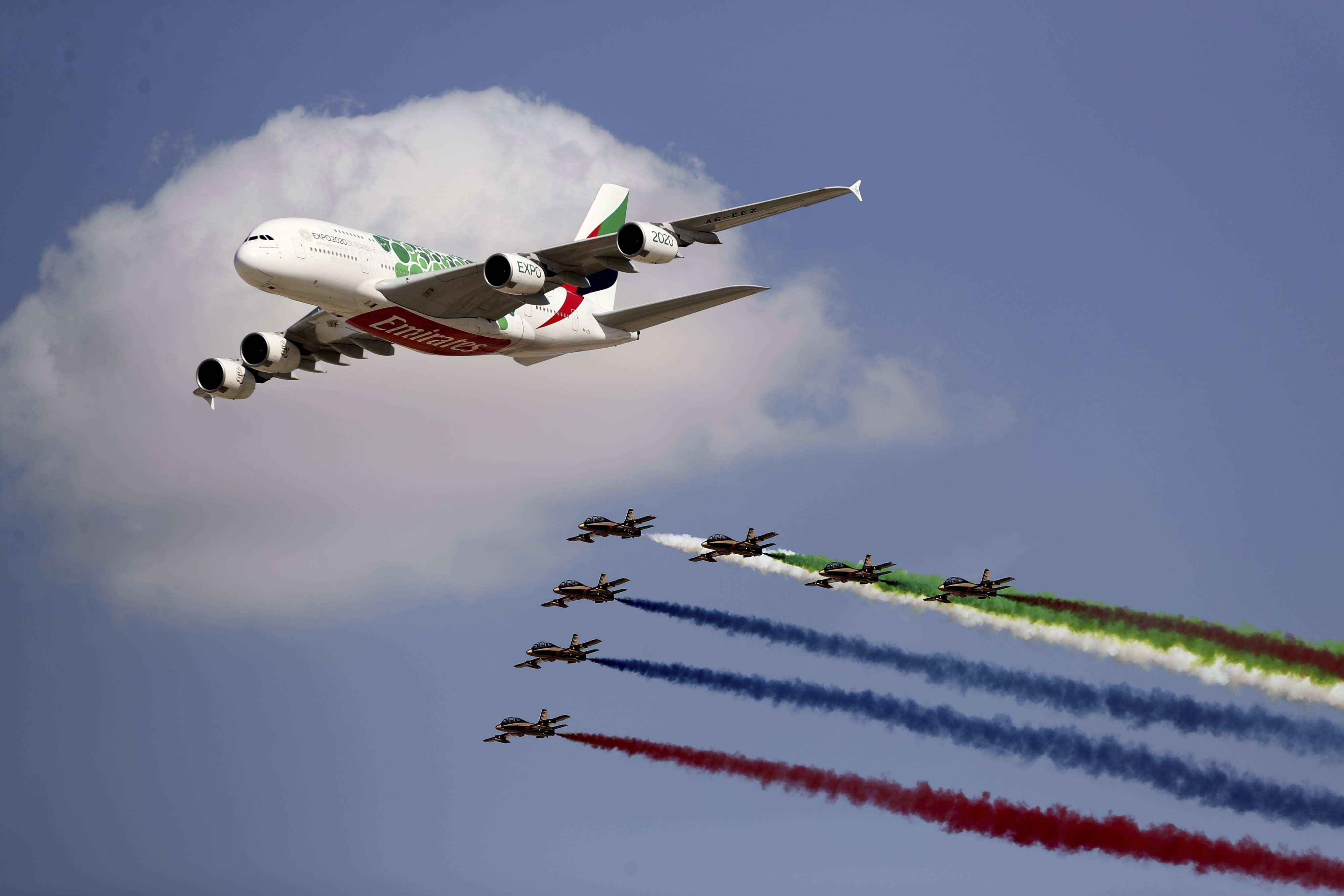 """FILE - In this Nov. 17, 2019 file photo, an Emirates Airline A-380 leads the """"Al Fursan,"""" or the Knights, UAE air force aerobatic display team during the opening day of the Dubai Airshow, in Dubai, United Arab Emirates. On Sunday, March 22, 2020, long-haul carrier Emirates said it would suspend all passenger flights beginning Wednesday, March 25, 2020, over the effects of the coronavirus pandemic. (AP Photo/Kamran Jebreili, File)"""