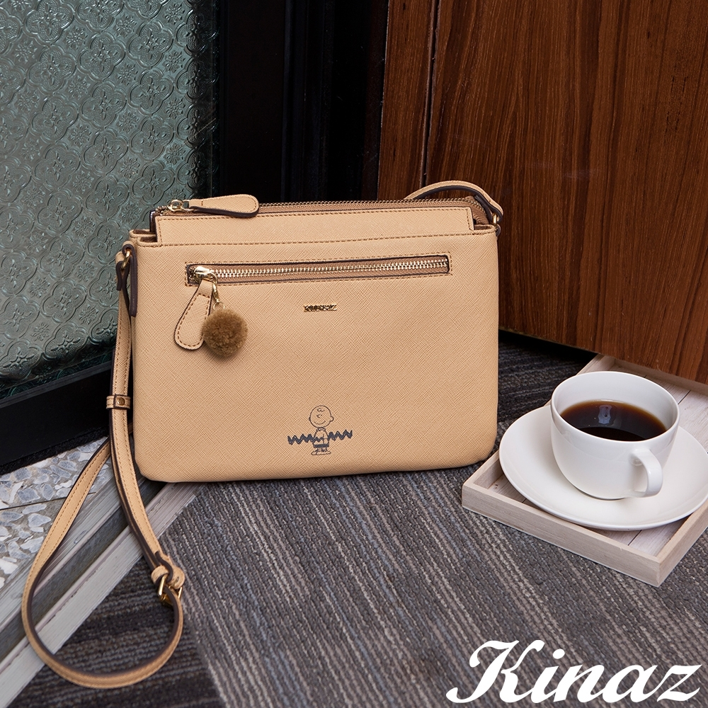 KINAZ 查理布朗聯名款 輕巧雙層扁型毛球斜背包-微笑奶蜜黃-心動系列