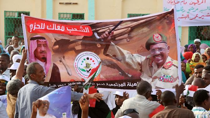 Supporters hold a banner during a campaign meeting for the incumbent Sudanese president and candidate for the National Congress Party Omar al-Bashir on March 31, 2015 in the capital Khartoum