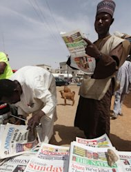 People read local newspapers with the headline 'We've killed 7 foreign hostages' on a street in Kano, Nigeria, Sunday, March. 10, 2013. The United Kingdom's military says its warplanes recently spotted in Nigeria's capital city were there to move soldiers to aid the French intervention in Mali, not to rescue kidnapped foreign hostages. The Ministry of Defense said Sunday that the planes had ferried Nigerian troops and equipment to Bamako, Mali. An Islamic extremist group in Nigeria called Ansaru partially blamed the presence of those planes as an excuse for claiming Saturday that it killed seven foreign hostages it had taken. ( AP Photo/Sunday Alamba)