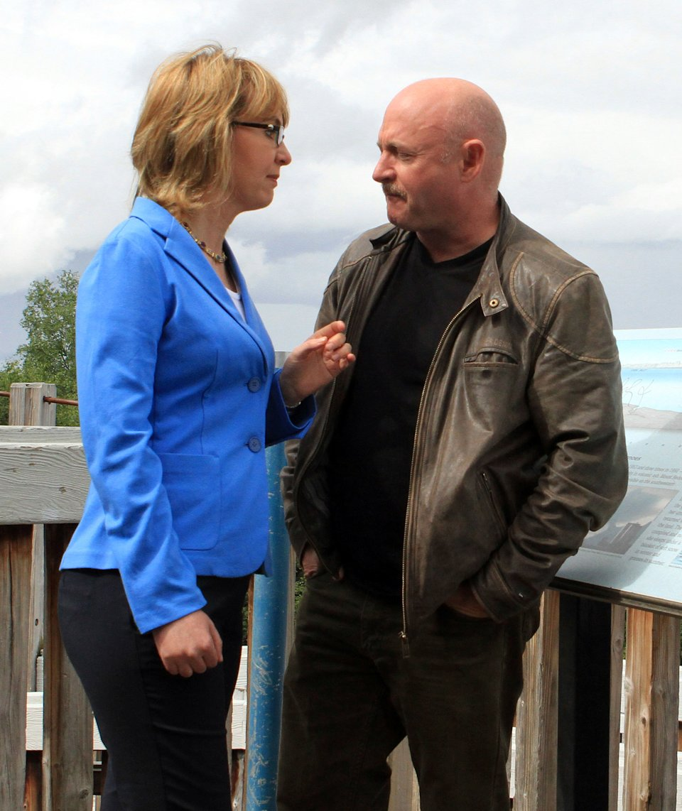 "CORRECTS SPELLING TO GABRIELLE NOT GABRIEL Former U.S. Rep. Gabrielle Giffords, D-Ariz., and her husband, former astronaut Mark Kelly, stand at an overlook of Cook Inlet in Resolution Park on Tuesday, July 2, 2013, in Anchorage, Alaska. Giffords and Kelly are in Alaska as part of a seven-state ""Rights and Responsibilities Tour"" urging members of Congress to expand background checks on gun sales. Giffords, who survived a 2011 assassination attempt, and Kelly founded Americans for Responsible Solutions. (AP Photo/Dan Joling)"