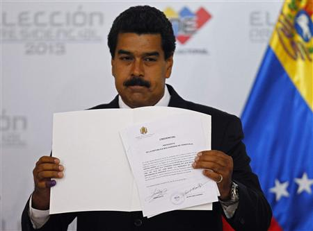 Venezuela's President-elect Nicolas Maduro holds the certificate given him by the National Electoral Council (CNE), confirming him as winner of Sunday's election, in Caracas, April 15, 2013. REUTERS/Carlos Garcia Rawlins