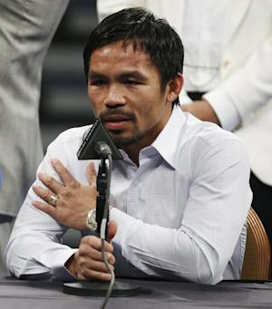 FILE - In this May 2, 2015 photo, Manny Pacquiao answers questions during a press conference following his welterweight title fight against Floyd Mayweather Jr. in Las Vegas. Boxing fans across the country or at least their lawyers are calling the hyped-up fight between Pacquiao and Floyd Mayweather a fraud. Some 31 class action lawsuits had been filed through Friday alleging primarily the same thing: that Pacquiao's pre-existing shoulder injury should have been disclosed to fans ahead of time. (AP Photo/John Locher,File)