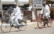 Muslim men ride on bicycles on a street in Kano, Nigeria, Sunday, March. 10, 2013. The United Kingdom's military says its warplanes recently spotted in Nigeria's capital city were there to move soldiers to aid the French intervention in Mali, not to rescue kidnapped foreign hostages. The Ministry of Defense said Sunday that the planes had ferried Nigerian troops and equipment to Bamako, Mali. An Islamic extremist group in Nigeria called Ansaru partially blamed the presence of those planes as an excuse for claiming Saturday that it killed seven foreign hostages it had taken. ( AP Photo/Sunday Alamba)