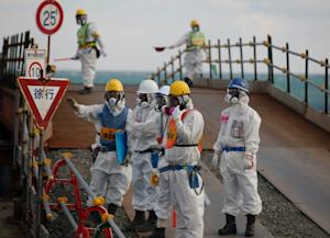 Workers, wearing protective suits and masks, are seen…