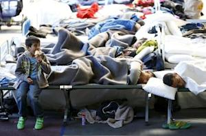 Migrants rest at an temporary shelter in a sports hall…