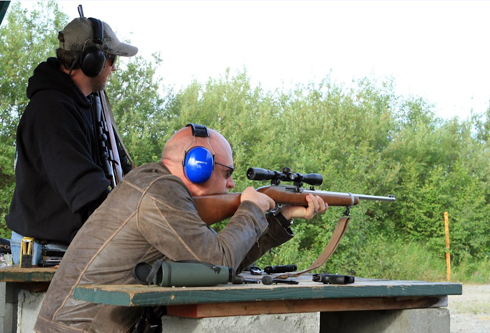 "Former astronaut Mark Kelly fires a hunting rifle at a shooting range on Tuesday, July 2, 2013, in Anchorage, Alaska, as Anders Gustafson spots bullet placement on the target. Kelly and his wife, former U.S. Rep. Gabrielle Giffords, are in Alaska as part of a seven-state ""Rights and Responsibilities Tour"" urging members of Congress to expand background checks on gun sales. Giffords, who survived a 2011 assassination attempt, and Kelly founded Americans for Responsible Solutions. (AP Photo/Dan Joling)"